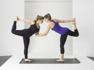 two women doing yoga to help getting pregnant