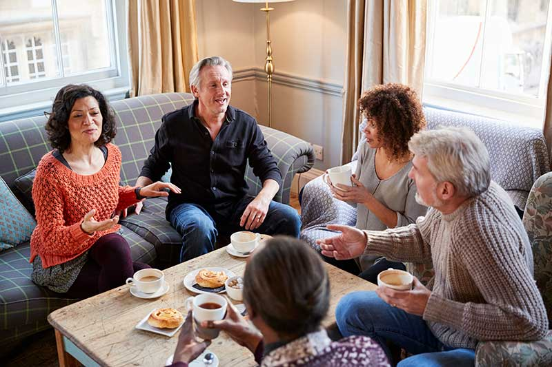 image of a group people having a discussion around a coffee table